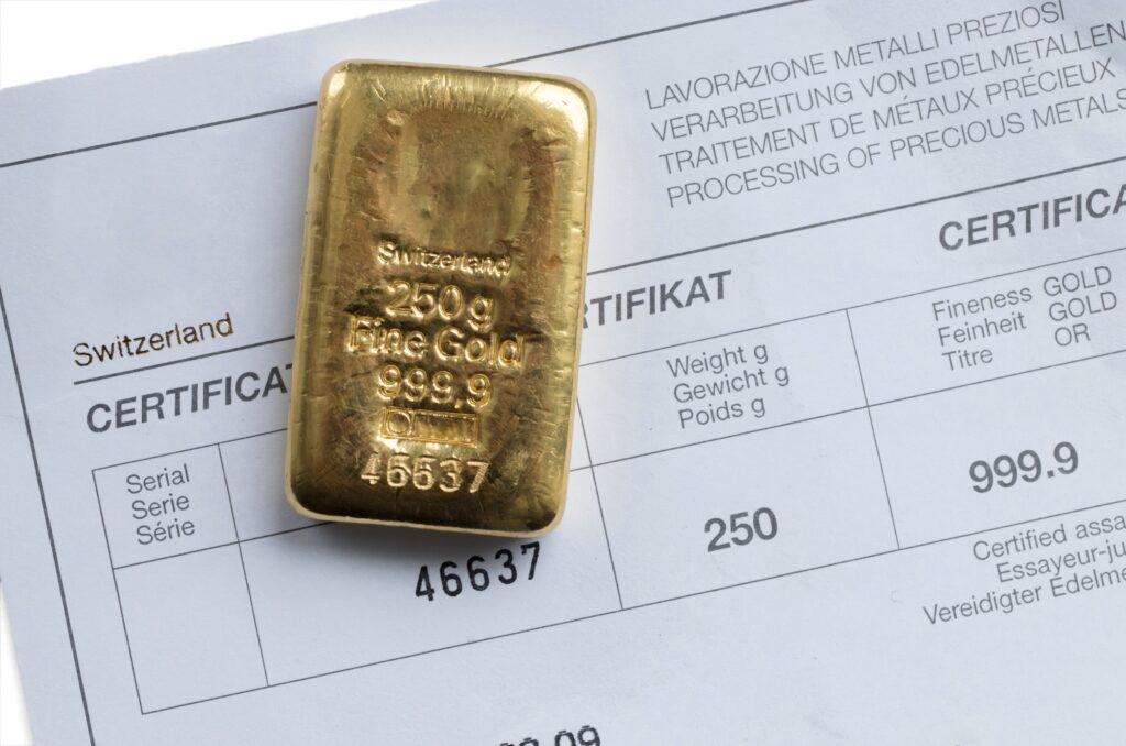 Ein 250 g Goldbarren auf einem Zertifikat des Herstellers liegend